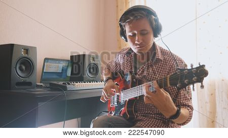 Young musician composes and records music playing the guitar, using computer, from the front view