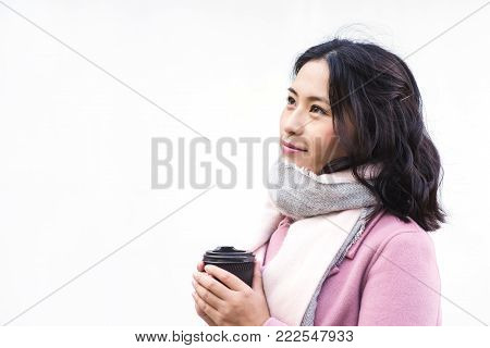 Beautiful young asian woman drinking hot drink from disposable paper cup outdoors on white background. Lookup. Girl dressed in pink coat and white scarf.