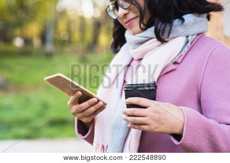 Beautiful young asian woman drinking hot drink from disposable paper cup outdoors. A girl with glasses looks into phone.