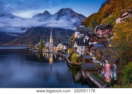 Scenic picture-postcard view of famous Hallstatt mountain village with Hallstaetter Lake in the Austrian Alps in fall during twilight, region of Salzkammergut, Austria