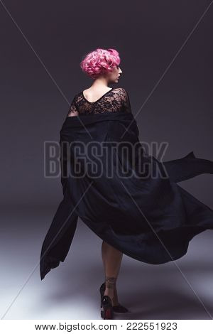back view of pin up girl in cloak infront of grey background
