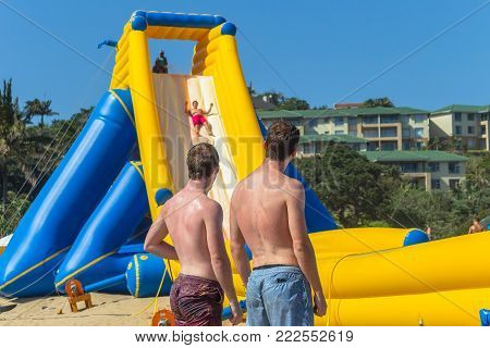 Beach Summer holidays amusment public boys girls thrill rides down high water slide yellow blue air inflated structure .