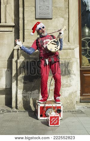 Lvov, Ukraine - 01.04.2017: Artist in Santa Claus red costume sings and plays electric guitar