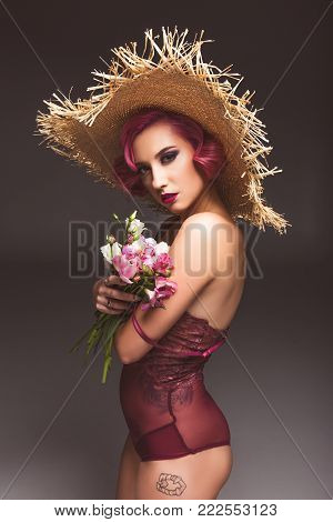 pretty pink haired curly girl in straw hat posing with flowers infront of grey background