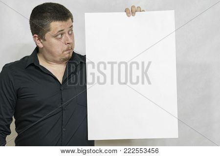 A man is holding an empty scoreboard or white square of paper. The face is surprised. On a white background. copyspace