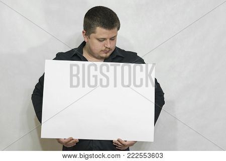 A man is holding an empty scoreboard or white square of paper. On a white background. copyspace