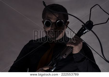 Crossbow in the hands of a young man. A man in dark camouflage glasses. Finger on the trigger.