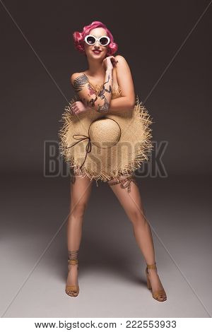 pretty naked pin up girl in sunglasses covering by straw hat infront of grey background