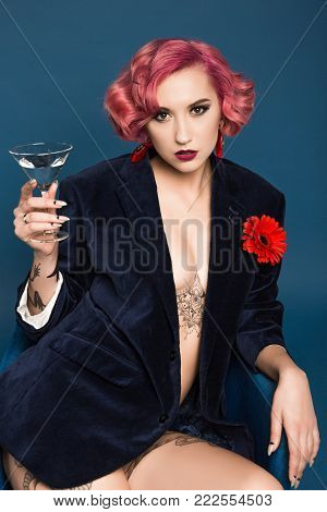beautiful tattoed pin up girl in jacket with boutonniere and wineglass infront of blue background