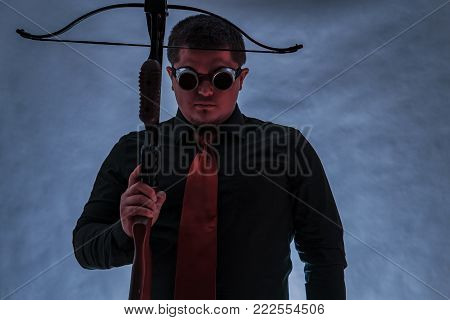 The arboleth in the hands of the young man is pointing upwards. A man in dark camouflage glasses. Finger on the trigger.