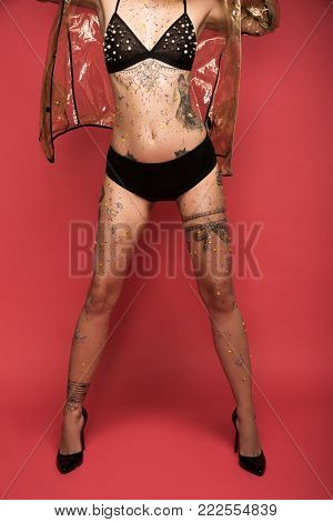 woman with tattoos in lingerie and raincoat infront of red background