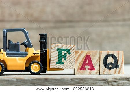 Toy yellow forklift hold letter block F to complete word FAQ (Abbreviation of Frequently asked questions) on wood background