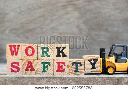 Toy forklift hold letter block Y to complete word work safety on wood background