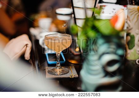 Cocktail glasses filled with alcoholic drinks on the bar counter against the background of dark bar hall