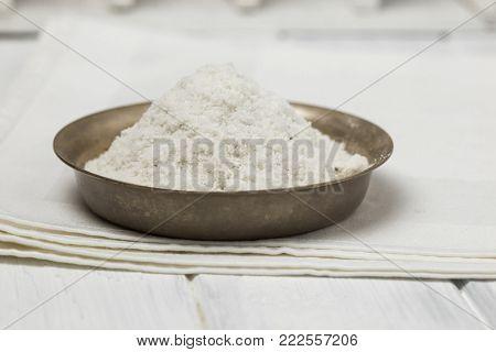 salt fine grind on a rustic table. Natural sea salt is bright white.