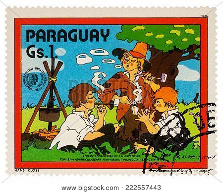 Moscow, Russia - January 18, 2018: A stamp printed in Paraguay shows Huckleberry Finn and Friends by Campsfire, Adventures of Tom Sawyer by Mark Twain, series