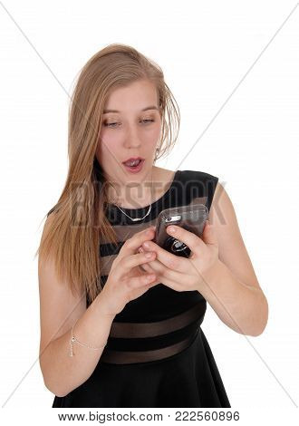 A lovely blond woman in a black dress looking in disbelief at her cell phone is disgusted about the message, isolated for white background