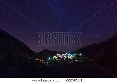 Night view of mountain village, Atlas mountains, Africa. Starry night sky.