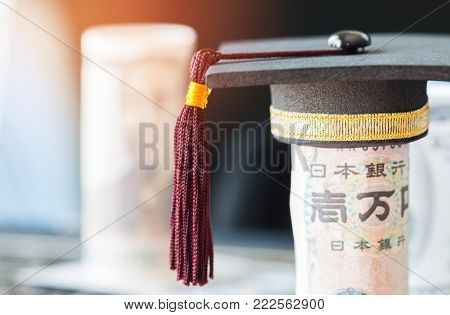 Concept of international graduate study aboard, graduation black cap on pile of foreign money Asian, JPY, EURO money. Education certificate of Abroad program. Vintage stlye
