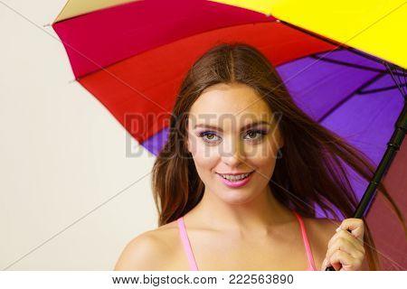 Woman Standing Under Colorful Rainbow Umbrella