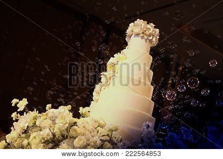 White floral wedding cake with bubble at wedding reception