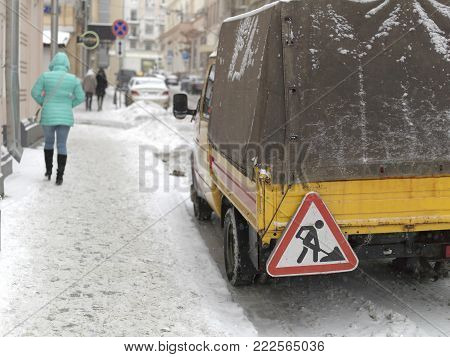 Rear of a truck with Works Ahead sign on a street covered with snow
