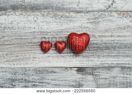 Three Red Love Shinny Hearts on wooden Texture Background with copyspace