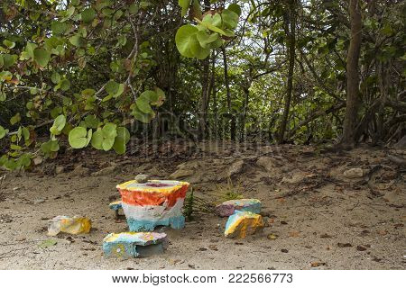 A grinding table with indentation and stone grinder made out of brightly painted pieces of concrete and rocks by the beach and tropical foliage in the Yucatan Mexico
