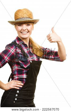 Gardening concept. Attractive woman in dungarees and pink check shirt and sun hat showing thumb up. Isolated background