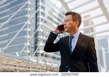 medium aged asian business man wearing modern black suit making phone call with mobile smart phone in building city background, internet network connection, technology communication, financial concept