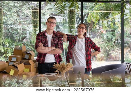 start up small business owner smiling at workplace. freelance man & woman seller posing at their shop.  Online selling, e-commerce, shipping concept