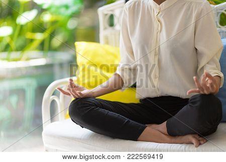 woman make yoga pose meditating while sitting on sofa at home