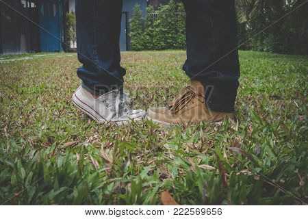 Legs Of Girlfriend Standing On Tiptoe Close To Boyfriend Outdoors. Woman Kissing Man In Park. Couple