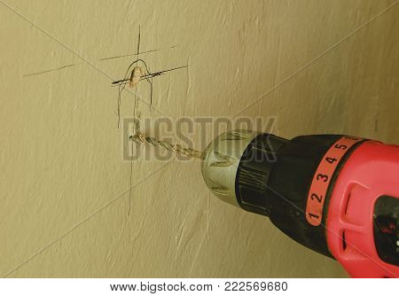 Closeup of drill machine. Drilling hole in the wall