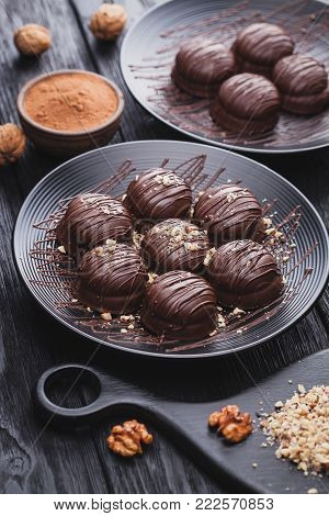 delicious fresh mini chocolate cakes with walnut on a black wooden table