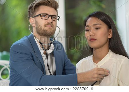 doctor listening to patient heartbeat with stethoscope