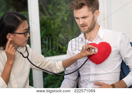 Woman doctor checking patient's vitals man listening to heartbeat with stethoscope over red pillow heart shape on his chest.