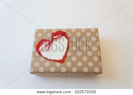 Gift box wrapped in brown paper with white polka dots topped with paper hearts tied with a red ribbon, valentine love, copy space, horizontal aspect