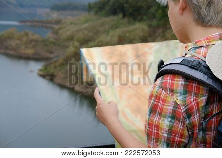 Traveler Man With Map, Backpack Travel At Forest & Lake In Summer. Tourist Backpacker Relaxing Outdo