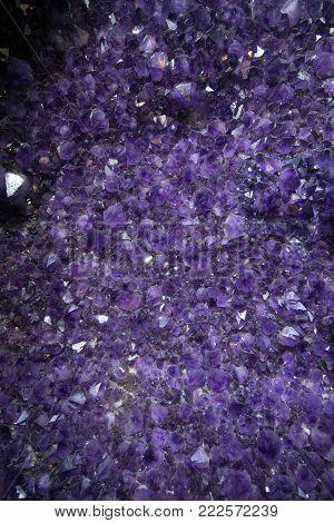 Crystal stone mineral surface, purple rough amethyst quartz crystals an Amethyst crystal geode. semiprecious gem