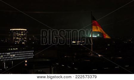 German Flag on Reichstag, Berlin, night view with city lights in the background