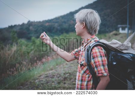 Traveler Hiker Man With Backpack Searching Direction Near Lake. Tourist Backpacker Holding Compass S