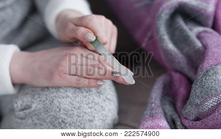 Attractive young woman doing manicure at home, girl filing shaping nails with emery board lying on s