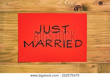 Image of text just married on the red paper on wooden table.