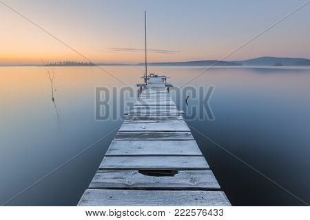 frosty dawn on lake with old wooden pier