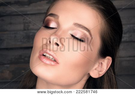 Close-up portrait of a beautiful young woman with eyes closed against the dark wall. Professeonalny Nude makeup. Clean fresh skin