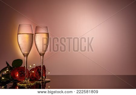 Champagne glasses, red roses in front of pink beige background. Valentines day holiday composition. Birthday, Women's, Wedding Day concept.