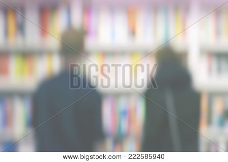 Silhouettes of two young people studying with interest bookshelves of books on bookshelves in library or in bookstore, for blurred backdrop. Concept interesting places to visit, life style