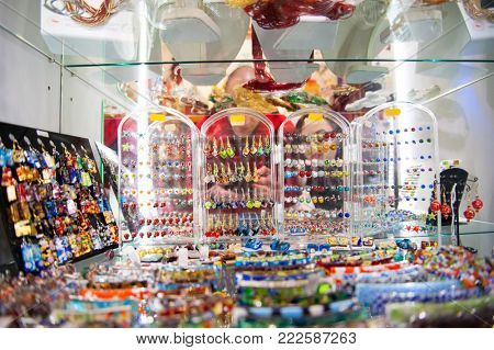 Colorful glass jewelry in the window case at the touristic jewelery shop in Italy