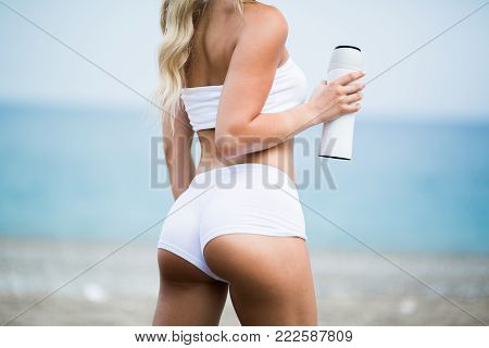 Gorgeous fit young woman with water bottle on the beach.